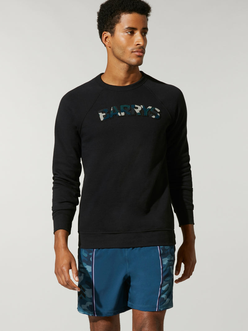 front view of male model in thin black sweatshirt with writing on chest and blue shorts
