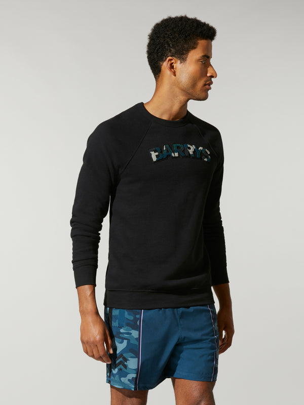side view of male model in thin black sweatshirt with writing on chest and blue shorts