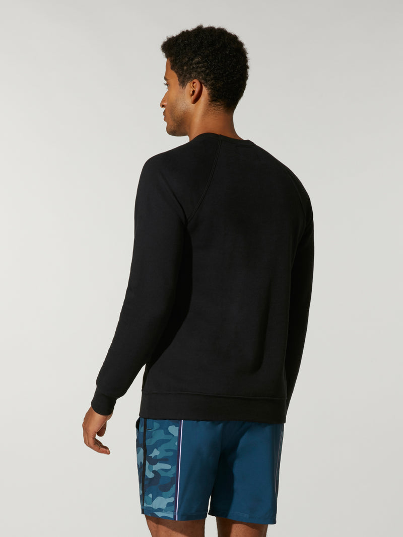 back view of male model in thin black sweatshirt with writing on chest and blue shorts