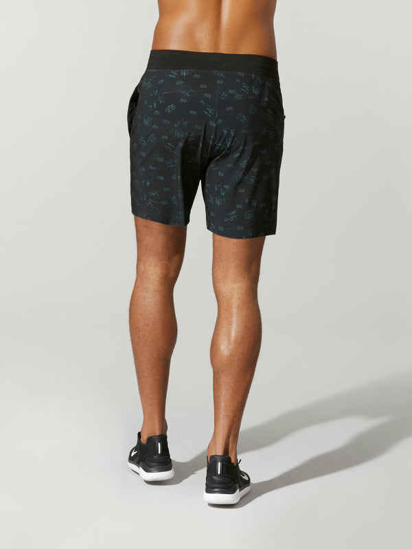back view of shirtless male model in black shorts and black sneakers
