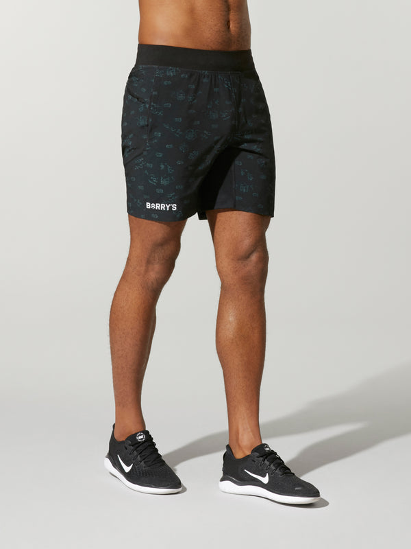 front view of shirtless male model in black shorts and black sneakers