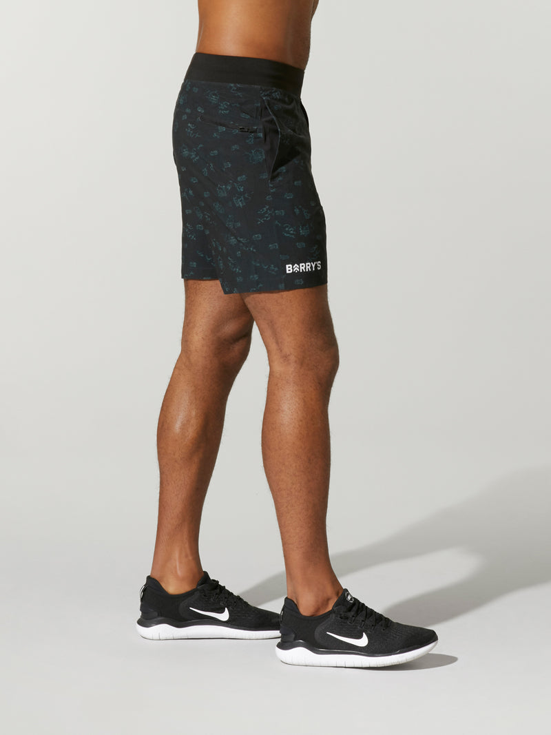 side view of shirtless male model in black shorts and black sneakers