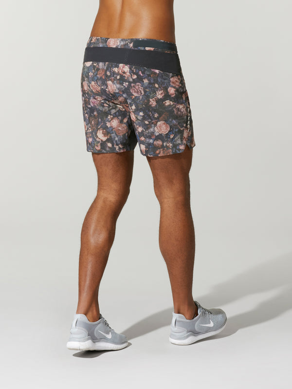 back view of shirtless male model in grey shorts with rose print