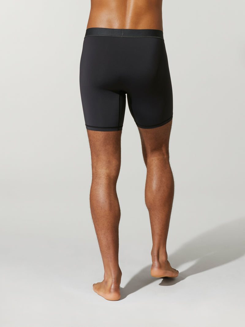 back view of shirtless male model wearing black compression shorts