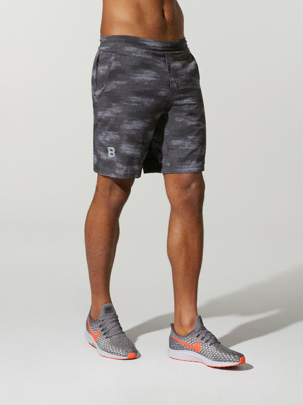 Model wearing gray patterned shorts that hit just above the knee