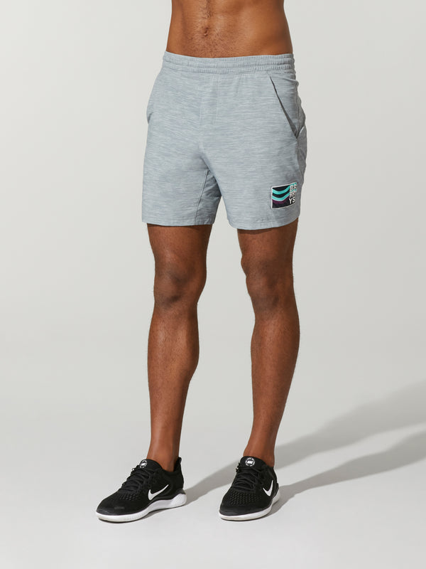 front view of shirtless male model in heather grey shorts and black sneakers