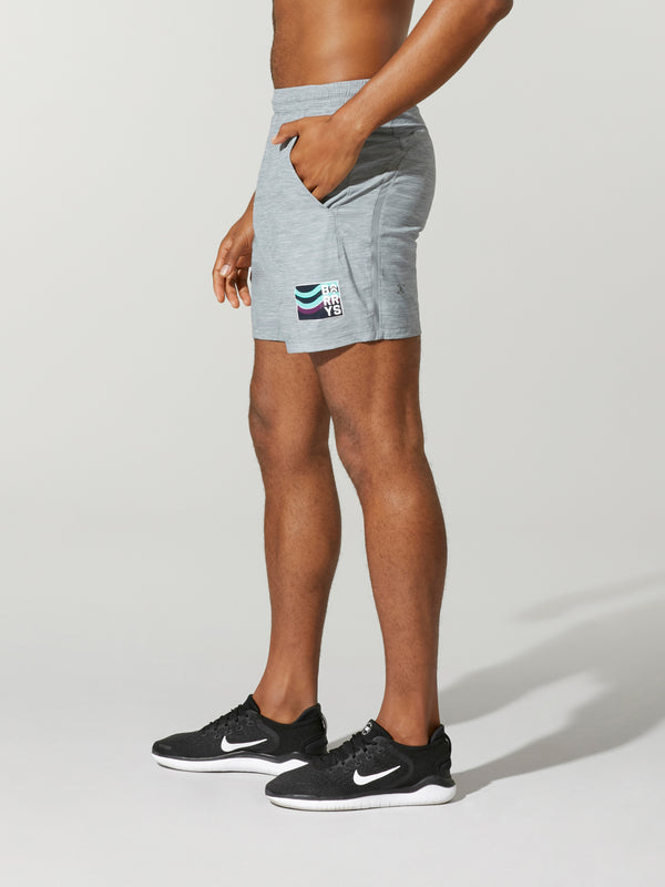 side view of shirtless male model in heather grey shorts and black sneakers