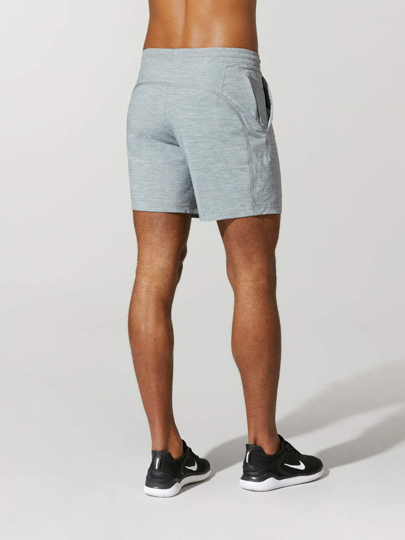 back view of shirtless male model in heather grey shorts and black sneakers