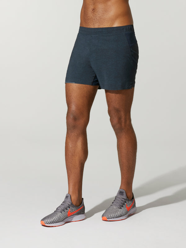 front view of shirtless male model in navy blue shorts and grey sneakers