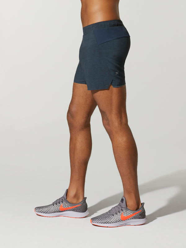 side view of shirtless male model in navy blue shorts and grey sneakers
