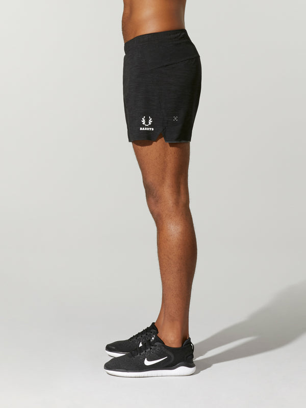 side view of male model in black workout shorts and black sneakers