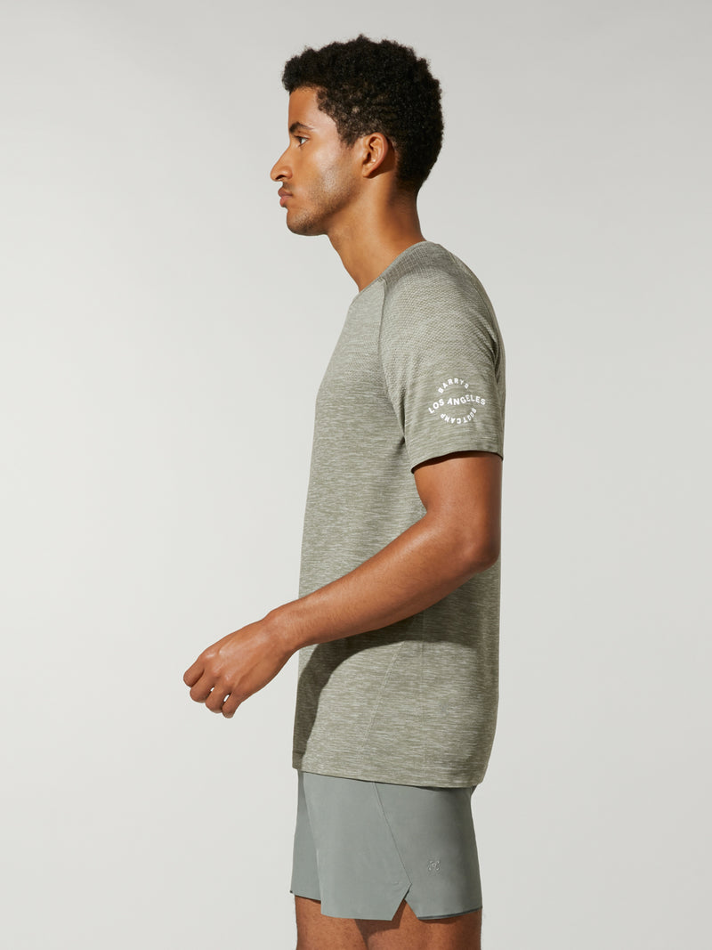 side view of male model in heather green t-shirt and matching athletic shorts