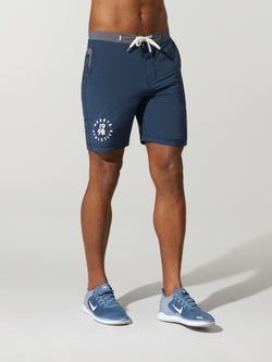 front view of shirtless male model in navy blue shorts with grey waisted and light blue sneakers