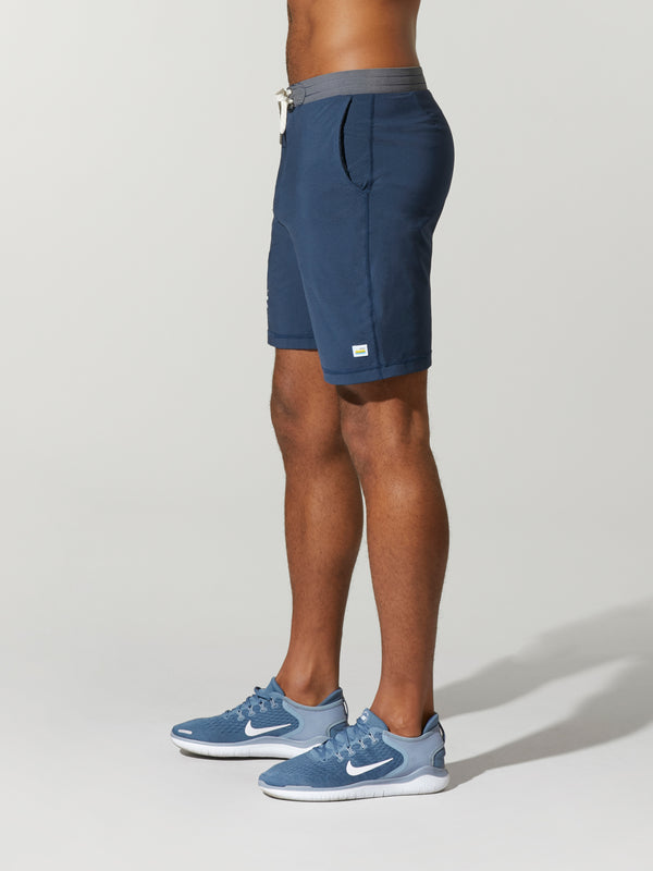 side view of shirtless male model in navy blue shorts with grey waisted and light blue sneakers