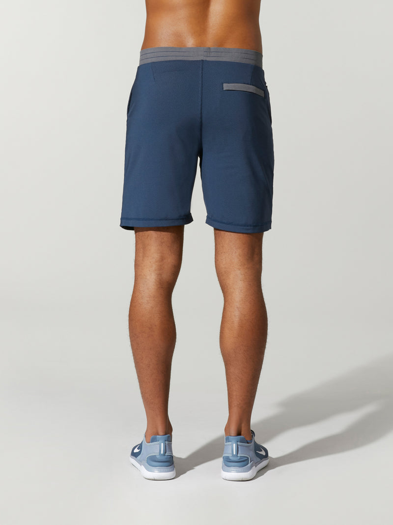 back view of shirtless male model in navy blue shorts with grey waisted and light blue sneakers
