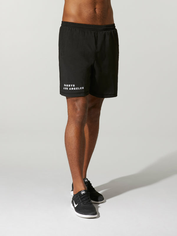 side view of shirtless male model wearing black barry's bootcamp athletic short