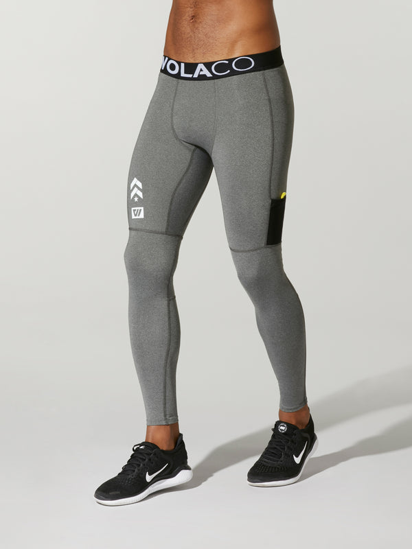 front view of male model in light grey leggings with black waistband and barry's bootcamp logo on front leg