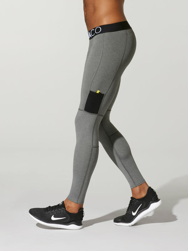 side view of male model in light grey leggings with black waistband and barry's bootcamp logo on front leg