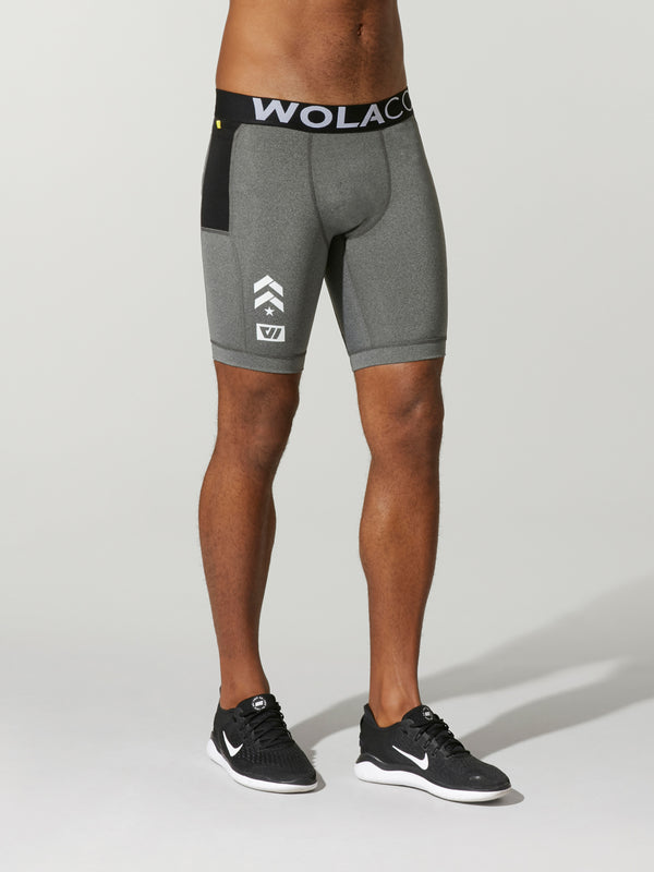 front view of male model in light grey compression shorts with black waistband and barry's bootcamp logo on front leg