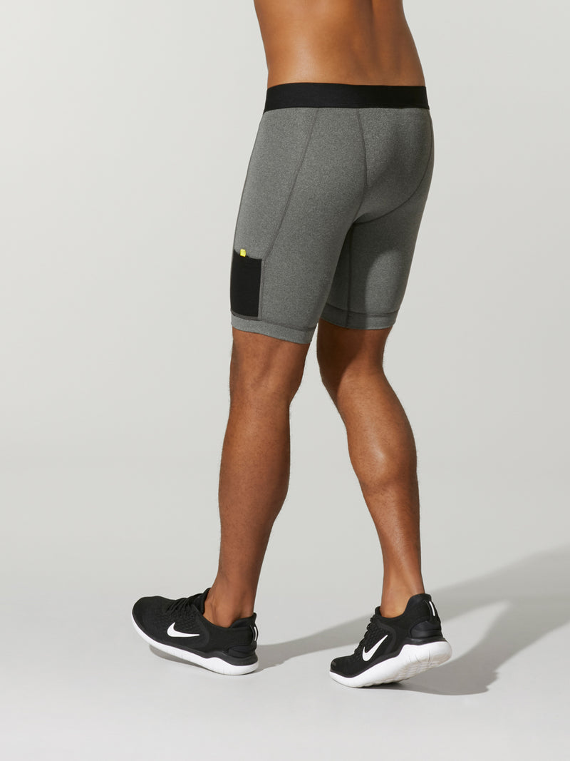 back view of male model in light grey compression shorts with black waistband and barry's bootcamp logo on front leg