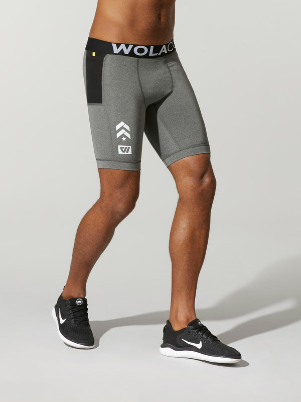 side view of male model in light grey compression shorts with black waistband and barry's bootcamp logo on front leg