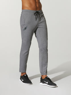 front view of shirtless male model in grey sweatpants and black sneakers