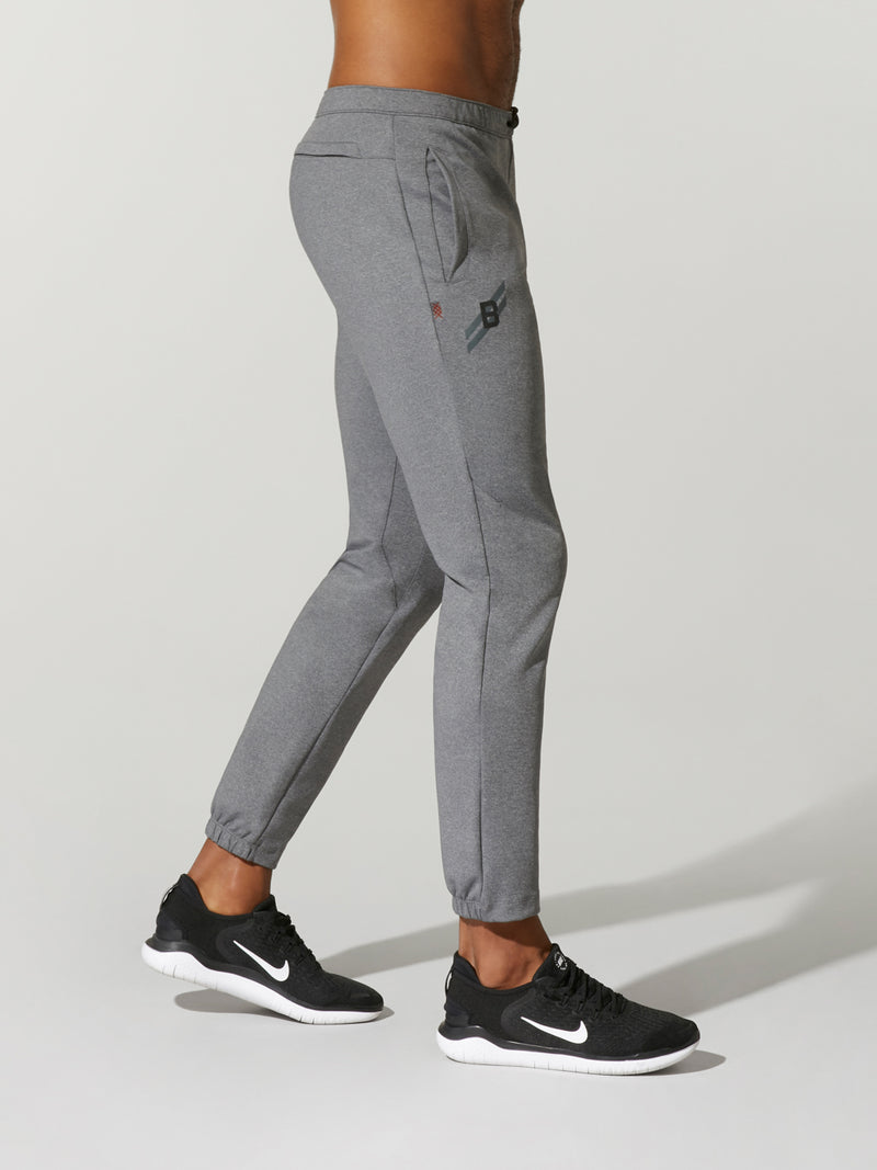 side view of shirtless male model in grey sweatpants and black sneakers