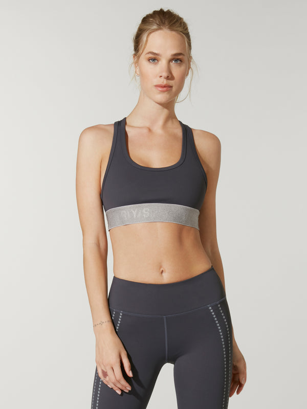 Front shot of model wearing dark grey FIT STORM TREAD BRA with light gray band