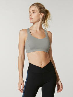 front view of model in light green sports bra and high waisted dip front black leggings