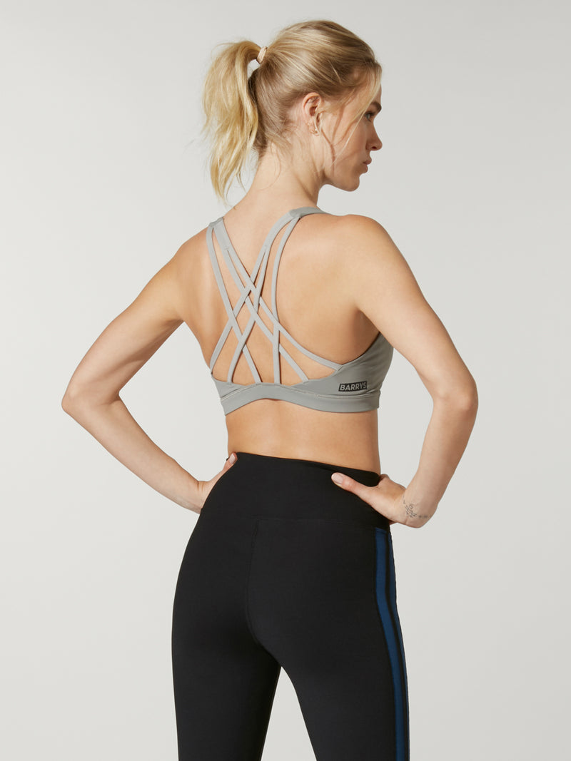 back view of model in light green sports bra and high waisted dip front black leggings