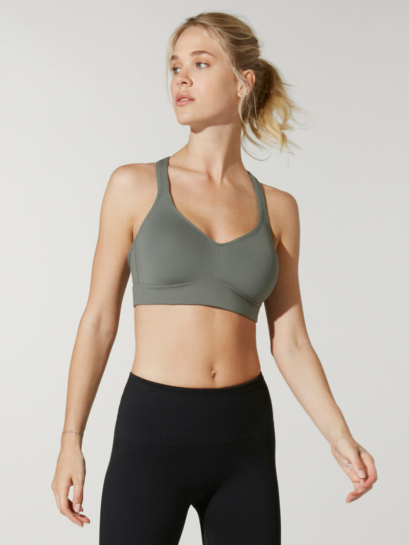 front view of model in grey green sports bra and black leggings