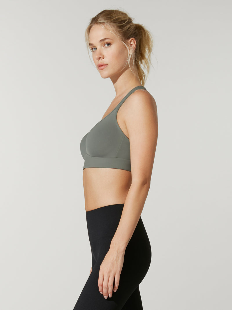 side view of model in grey green sports bra and black leggings