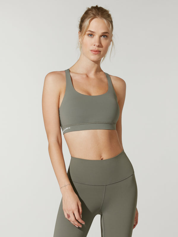 front view of model in olive green sports bra and matching olive green leggings