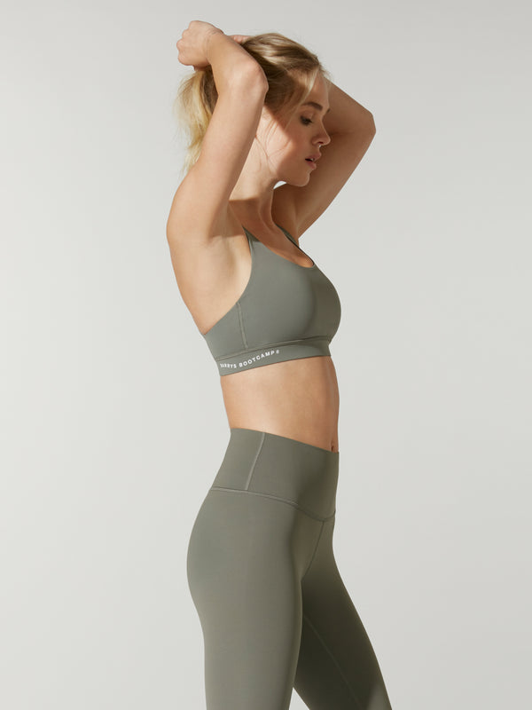 side view of model in olive green sports bra and matching olive green leggings