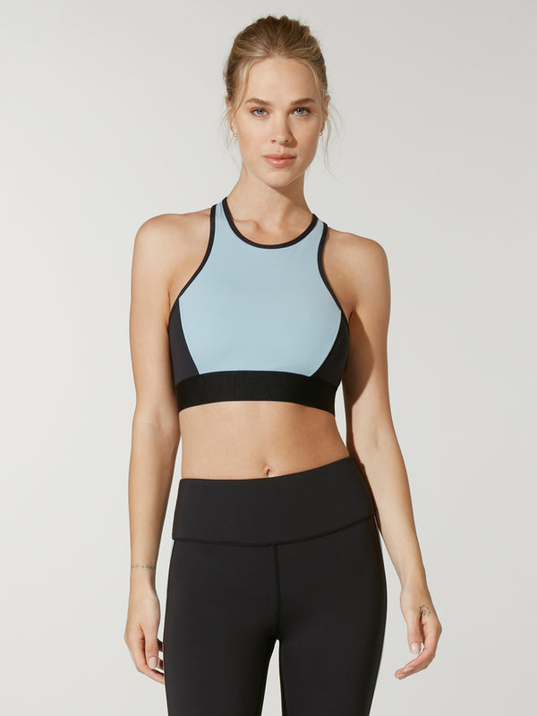 front view of model in light blue and black Alala long line sports bra and black leggings