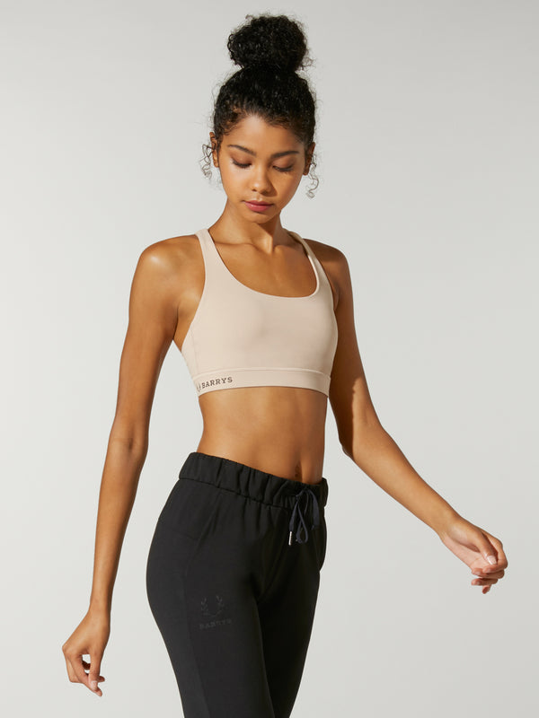 side view of model in light tan sports bra and high waisted black sweatpants