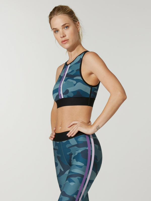 side view of model in blue camouflage sports bra with pink and white stripe in front ant matching blue camo leggings