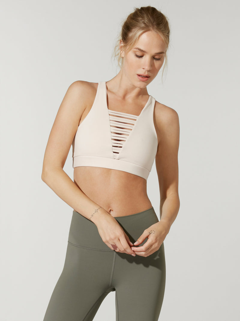 Front view of model in Barry's light pink 925 no strings attached sports bra with front caging detail and olive green leggings