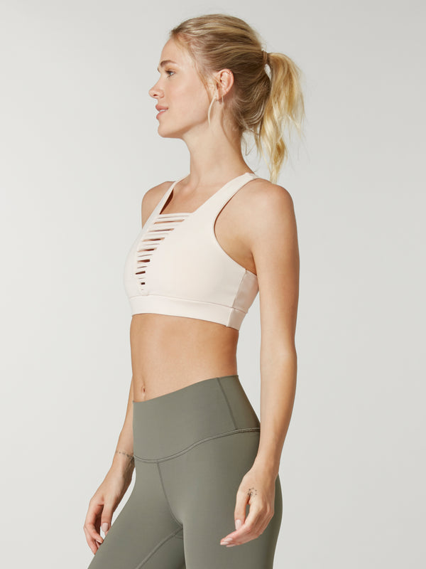 side view of model in Barry's light pink 925 no strings attached sports bra with front caging detail and olive green leggings
