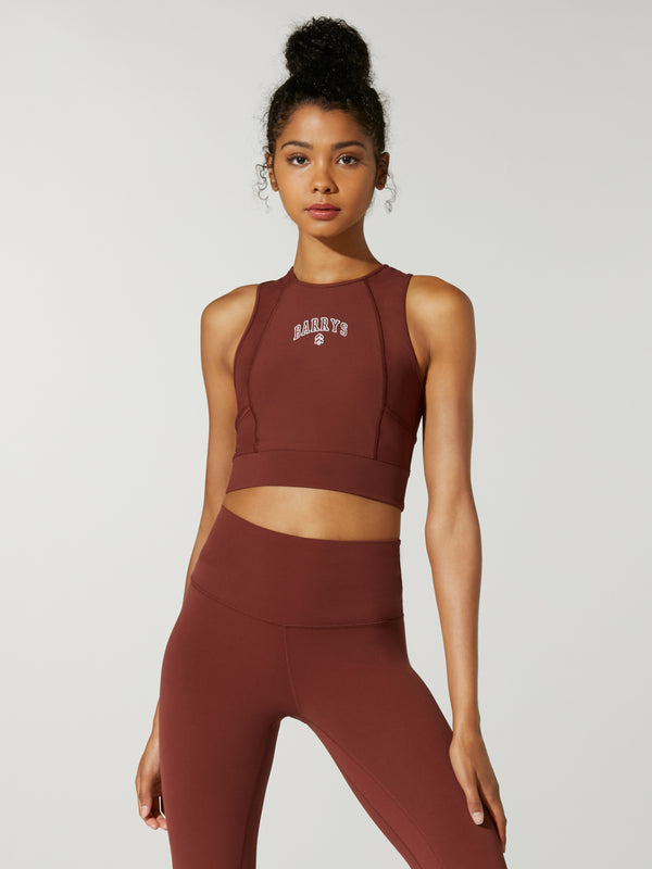 front view of model in dusty red cropped tank top and matching leggings
