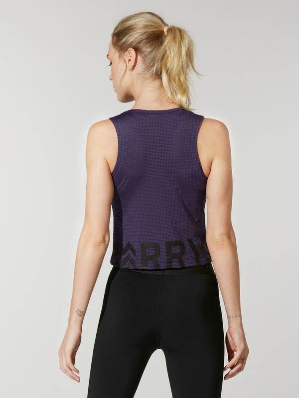 Back shot of model wearing dark purple FIT NIGHTSHADE CROP INTERVAL TANK with black Barry's logo on bottom