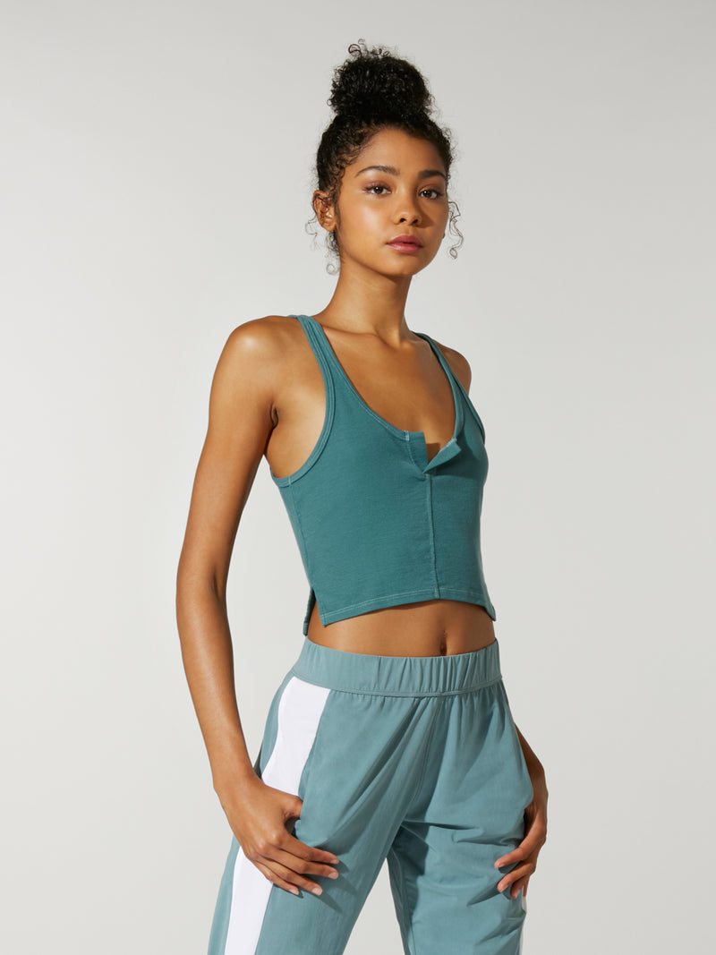 front view of model in cropped teal henley tank top and teal sweatpants with white stripe down leg