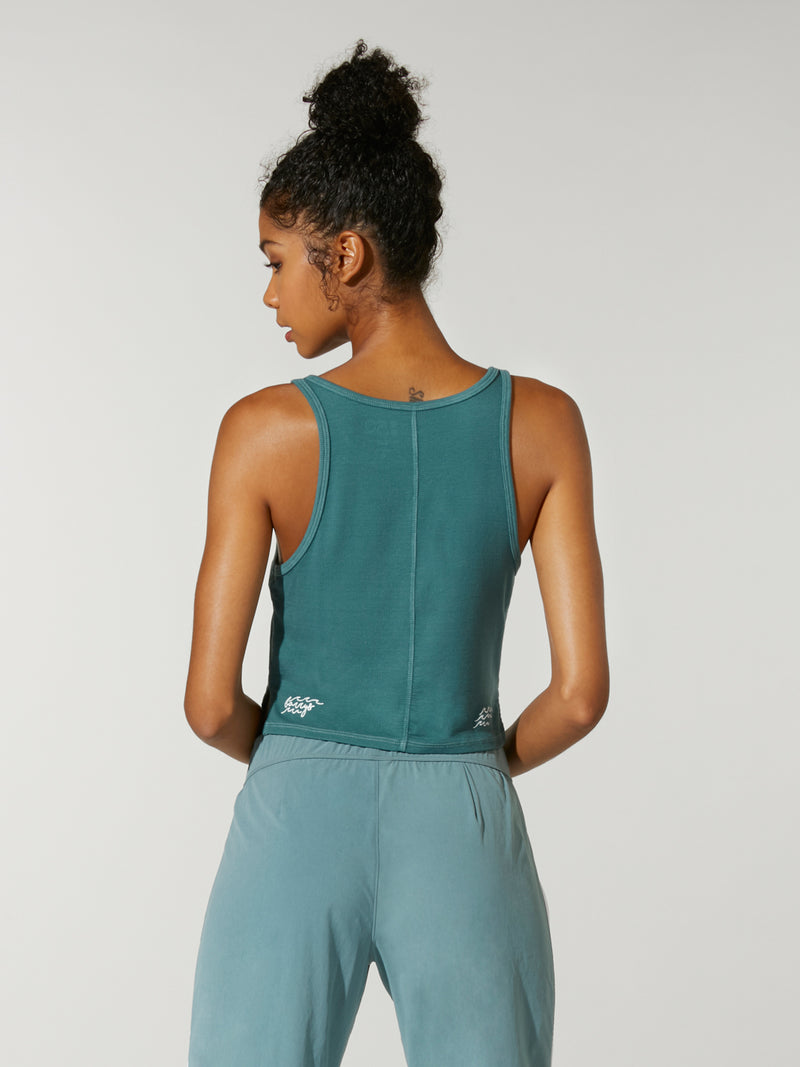 back view of model in cropped teal henley tank top and teal sweatpants with white stripe down leg