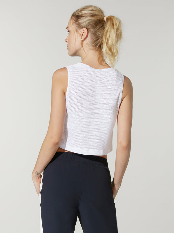 back view of model in white cropped muscle tank top with Barry's crew written on front and black sweatpants