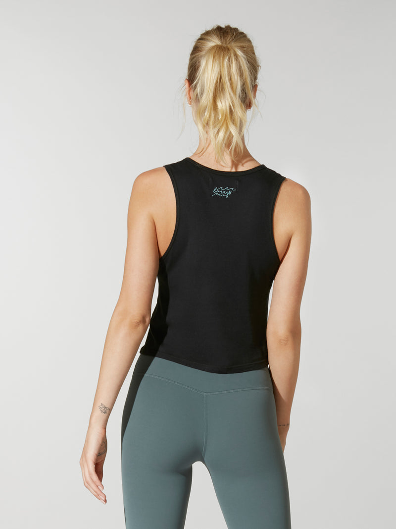 "back view of model in black cropped tank top with phrase ""beach, please"" in teal cursive lettering and teal leggings"