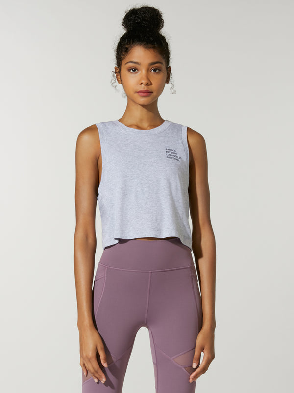 front view of model in light grey cropped muscle tank top and purple leggings