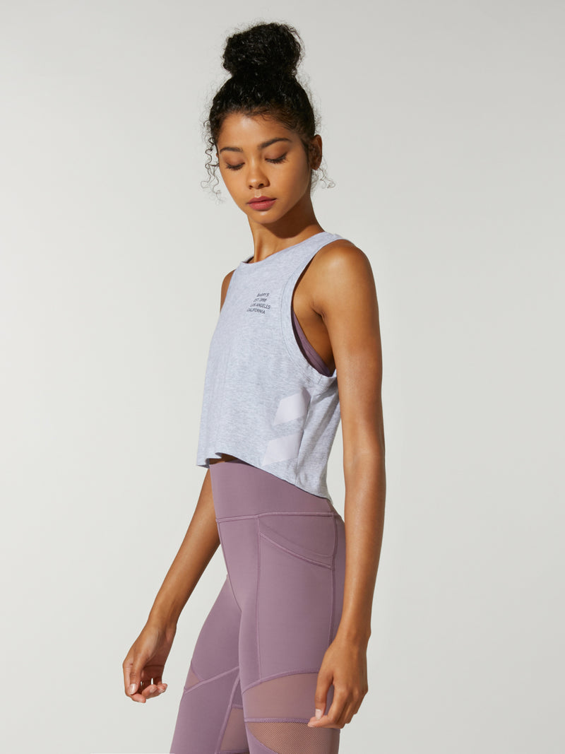 side view of model in light grey cropped muscle tank top and purple leggings