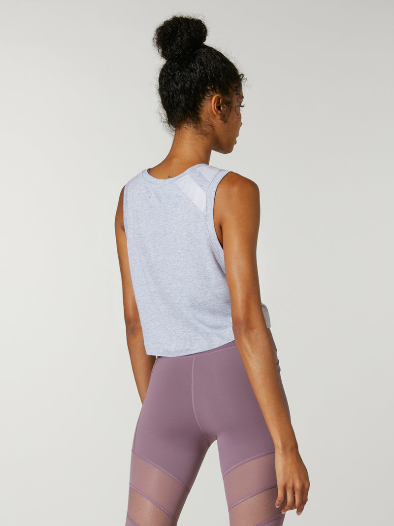back view of model in light grey cropped muscle tank top and purple leggings