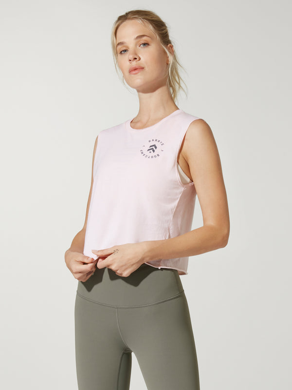 front view of model in light pink cropped muscle tank with small circular logo on chest and green leggings