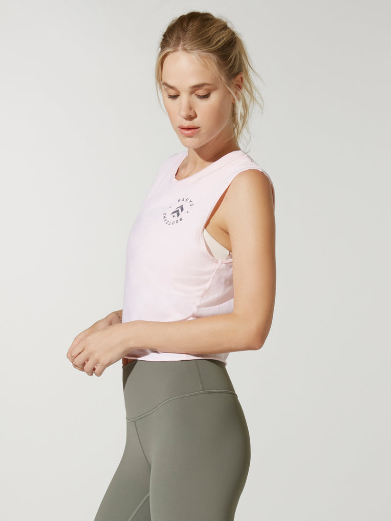 side view of model in light pink cropped muscle tank with small circular logo on chest and green leggings